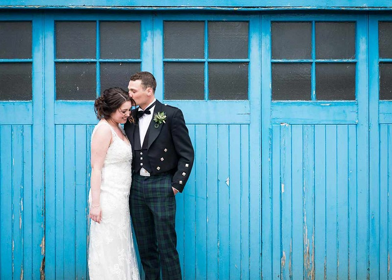 Couple hugging and kissing in front of blue garage doors